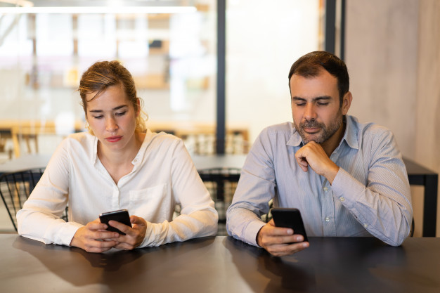 portrait-male-female-colleagues-using-phones-cafe_1262-17990